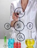 Donna chimico formule su vetro su sfondo grigio — Foto Stock