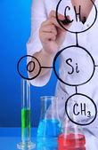 Mujer químico escribiendo fórmulas en vidrio sobre fondo azul — Foto de Stock