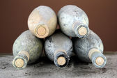 Old bottles of wine, on dark brown background — Stock Photo