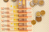 Euro banknotes and euro cents on beige background — Stock Photo