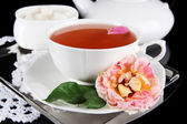 Konvice a šálek čaje z čajové růže na kovový zásobník na ubrousky černé pozadí — Stock fotografie