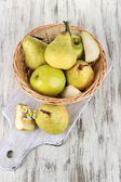 Pears in basket on board on wooden table — Stock Photo