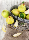 Pears in basket on braided tray on burlap on wooden table — Stock Photo