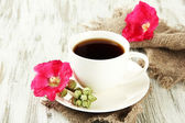Cup of coffee and pink mallow flowers on wooden background — Stock Photo