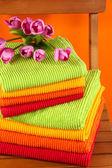 Handtücher und blumen auf holzstuhl auf orange hintergrund — Stockfoto