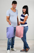 Beautiful loving couple is shopping on grey background — Stockfoto