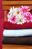 Towels and flowers on wooden chair on brown background — Stock Photo