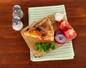 Pizza calzone on wooden board on napkin on wooden table — Stock Photo