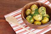 Vařené brambory na dřevěné misky na ubrousek na dřevěný stůl — Stock fotografie