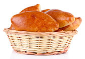 Fresh baked pasties in wicker basket, isolated on white — Stock Photo