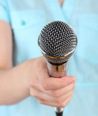 Female with microphone close-up background — Stockfoto