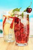 Verres de boissons aux fruits avec des glaçons sur fond bleu — Photo