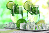 Glasses of cocktail with ice on metal tray on napkin on wooden table on nature background — Stock Photo