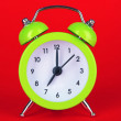 Green alarm clock on red background — Stock Photo #28370853