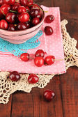 Ripe red cherry berries in bowl on wooden table close-up — Stock Photo