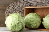 Cabbage on table on wooden background — Stock Photo