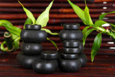 Spa stones and bamboo on bamboo mat background — Stock Photo