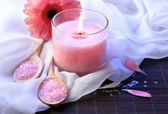 Beautiful pink candle with flower on bamboo mat — Stock Photo