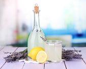 Lavender lemonade,in glass bottle, on violet wooden table, on bright background — Stock Photo