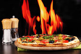 Delicious pizza with spices on wooden table on fire background — Stock Photo