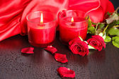 Beautiful romantic red candle with flowers, close up — Stock Photo
