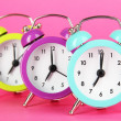 Colorful alarm clock on pink background — Stock Photo