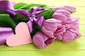 Piękny bukiet tulipanów fioletowy na zielonym tle drewniane — Zdjęcie stockowe