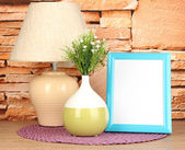 Colorful photo frame, lamp and flowers on wooden table on stone wall background — Stock Photo