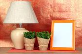 Marco colorido de la foto, una lámpara y flores en la mesa de madera sobre fondo rojo — Foto de Stock