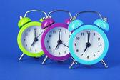 Colorful alarm clock on blue background — Stock Photo