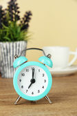 Blue alarm clock on table on beige background — Stock Photo