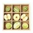 Sliced fruit in wooden box isolated on white — Stock Photo