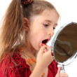 Little girl in her mother's dress, is trying painting her lips, isolated on white — ストック写真