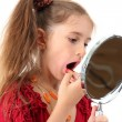 Little girl in her mother's dress, is trying painting her lips, isolated on white — Stock fotografie