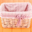 Wicket basket with pink fabric and bow, on color wooden background — Stok Fotoğraf #28527467