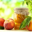 Постер, плакат: Jar of canned peaches and fresh peaches on wooden table outside