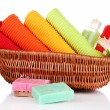 Stock Photo: Colorful towels, cosmetics bottles and soap in basket, isolated on white