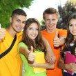 Happy group of young students standing in park — Stock Photo
