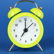 Green alarm clock on blue background — Stock Photo