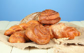 Composition with bread, rolls on sackcloth, on wooden table, on color background — Stock Photo