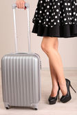 Girl's legs with suitcase in room — Stock Photo
