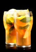 Iced tea with lemon and mint on black background — Stock Photo