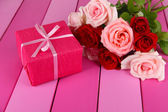 Beautiful bouquet of roses with gift on table close-up — Stock Photo