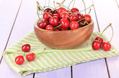 Cherry berries in bowl on wooden table close up — Stock Photo