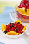 Useful fruit salad in glass cup and bowl on wooden table close-up — Stockfoto