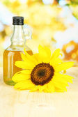 Oil in jar and sunflower on wooden table close-up — Stock Photo