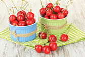 Cherry berries in bowls on wooden table close up — Stock Photo