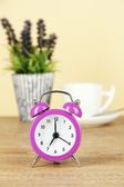 Purple alarm clock on table on beige background — Stock Photo