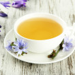 Stock Photo: Cup of tewith chicory, on wooden background