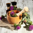 Medicine bottles and mortar with thistle flowers on wooden background — Stock Photo #28532967